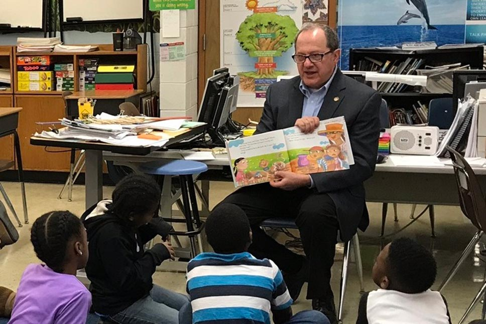 David Leland Reading To A Group Of Young Students